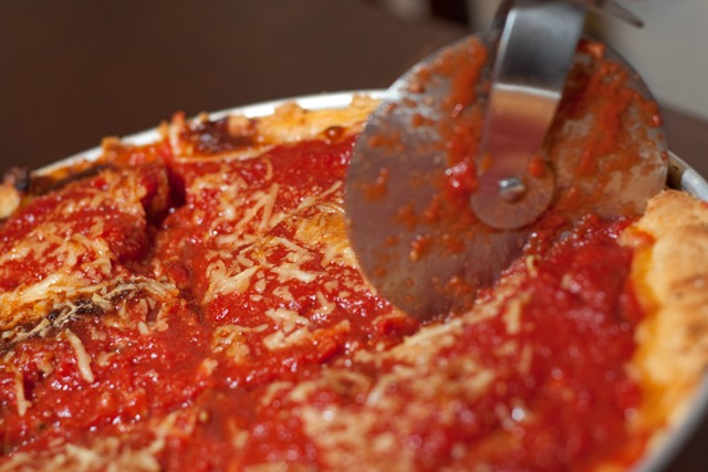 Cutting into a Chicago-Style Deep Dish Pizza